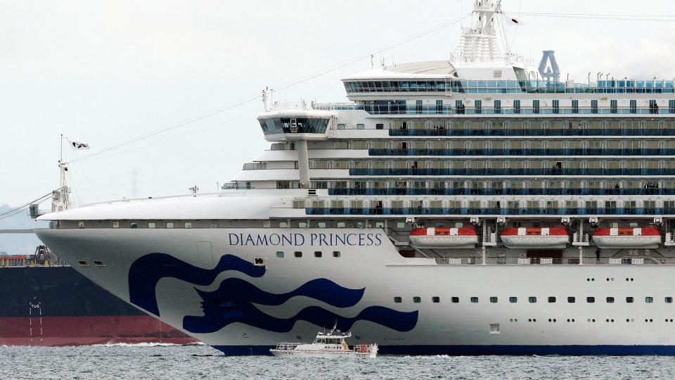 A small boat navigates near a cruise ship Diamond Princess anchoring off the Yokohama Port Tuesday, Feb. 4, 2020, in Yokohama, near Tokyo. (AP Photo/Eugene Hoshiko)