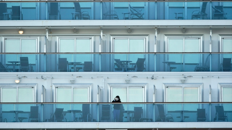 A passenger stands on the balcony of the cruise ship Diamond Princess anchored at the Yokohama Port, near Tokyo Thursday, Feb. 6, 2020. (AP Photo/Eugene Hoshiko)