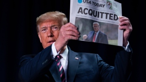 "U.S. President Donald Trump holds up a newspaper with the headline that reads ""ACQUITTED"" at the 68th annual National Prayer Breakfast, at the Washington Hilton, Thursday, Feb. 6, 2020, in Washington. (AP Photo/ Evan Vucci)"