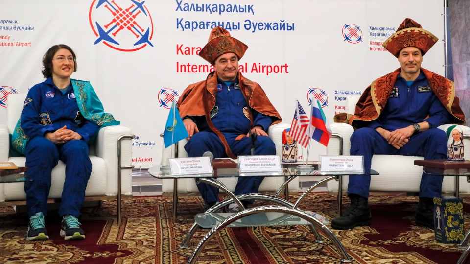 U.S. astronaut Christina Koch, left, Italian astronaut Luca Parmitano, right, and Russian cosmonaut Alexander Skvortsov dressed in a traditional Kazakh national attires attend a news conference in an airport of Karaganda, Kazakhstan, Thursday, Feb. 6, 2020. (Sergei Ilnitsky/Pool Photo via AP)