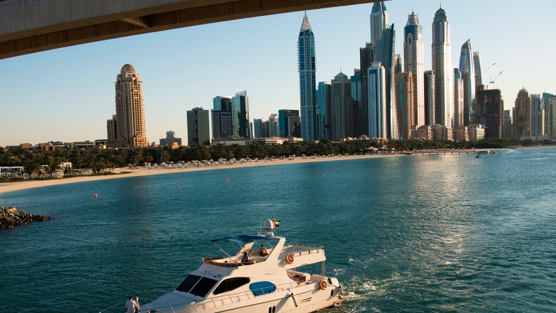 In this Dec. 21, 2019 file photo, a yacht passes under a bridge with the Dubai Marina seen in the background in Dubai, United Arab Emirates. (AP Photo/Jon Gambrell, File)