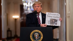 "President Donald Trump holds up a newspaper with a headline that reads ""Trump acquitted"" as he speaks in the East Room of the White House, Thursday, Feb. 6, 2020, in Washington. (AP Photo/Evan Vucci)"
