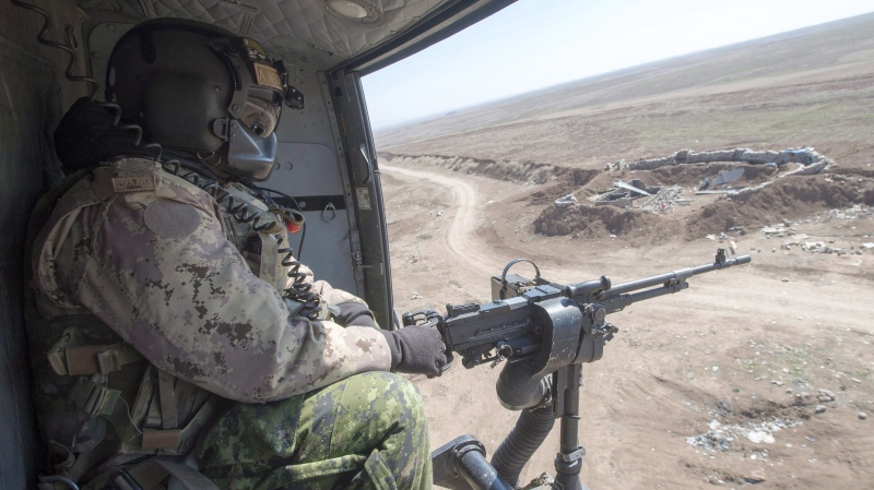 A Canadian Forces door gunner keeps watch as his Griffon helicopter goes on a mission, February 20, 2017 in northern Iraq. THE CANADIAN PRESS/Ryan Remiorz
