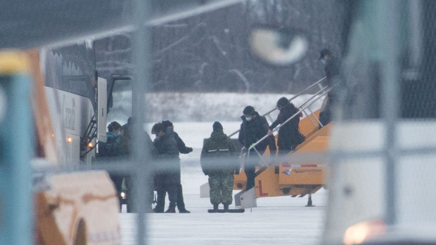 Passengers step off a plane carrying Canadians back from the Wuhan province in China, after it arrived at Canadian Forces Base Trenton in Trenton, Ont., on Friday Feb. 7, 2020. THE CANADIAN PRESS/Lars Hagberg
