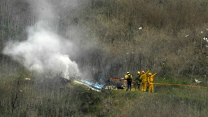 FILE - In this Jan. 26, 2020, file photo, firefighters work the scene of a helicopter crash where former NBA star Kobe Bryant died in Calabasas, Calif. U.S. (AP Photo/Mark J. Terrill, File)
