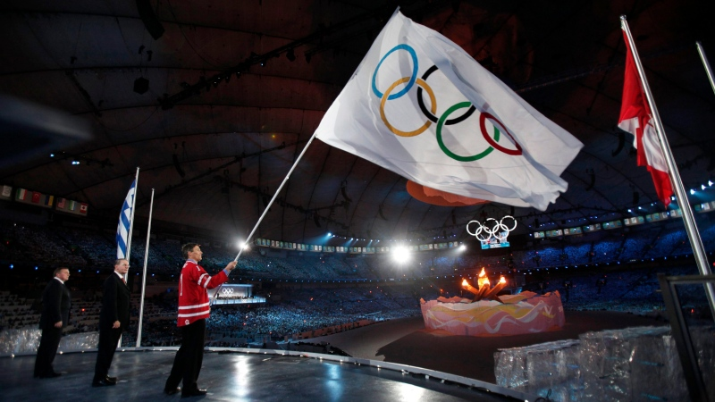 Former Vancouver mayor Gregor Robertson, right, waves the Olympic flag next to mayor of Sochi Anatoly Pakhomov, left, and International Olympic Committee (IOC) President Jacques Rogge, center, during the closing ceremony for the Vancouver 2010 Olympics on Feb. 28, 2010. (AP Photo/Jim Young, Pool)