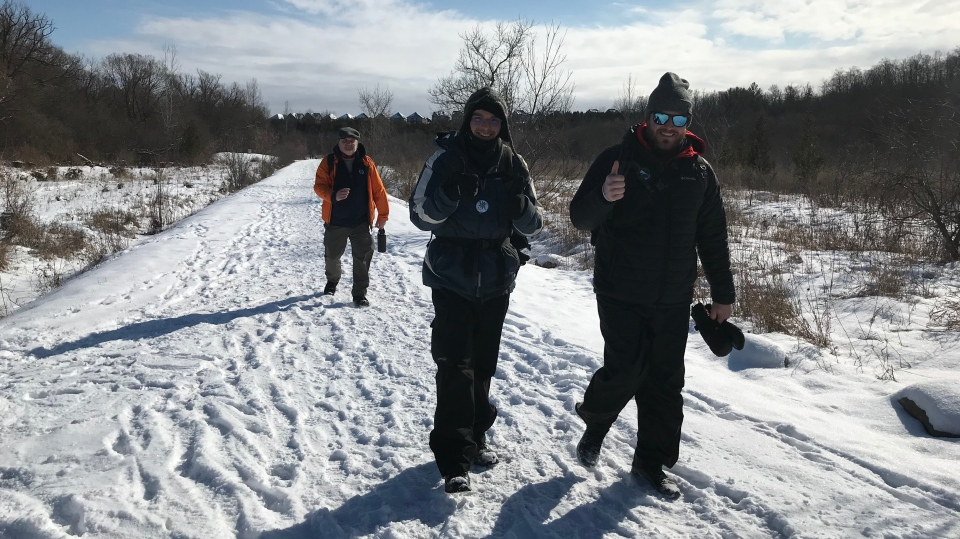 Three people walk on a snowy trail