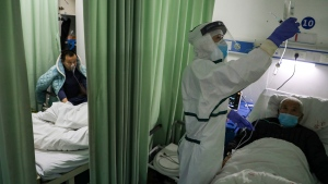 In this Thursday, Feb. 6, 2020, photo, a nurse checks on a patient in the isolation ward for 2019-nCoV patients at a hospital in Wuhan in central China's Hubei province. (Chinatopix via AP)