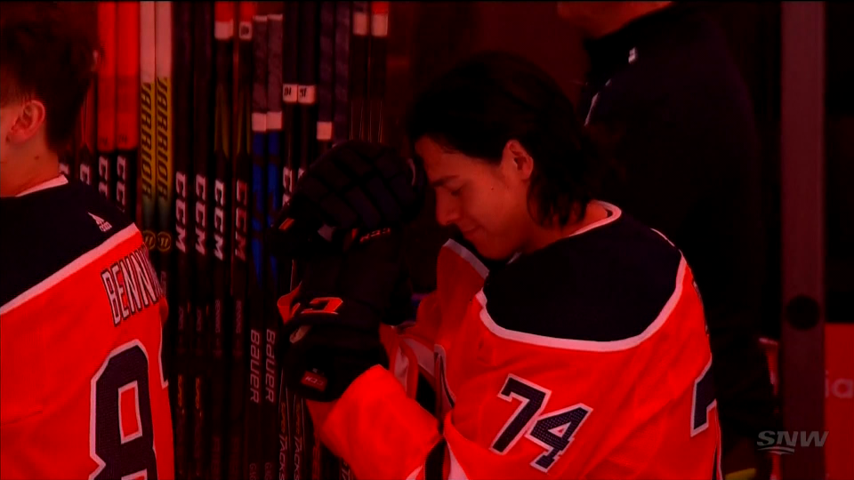 Oilers' No. 74 Ethan Bear bows his head during Kiya Bruno's English-Cree version of O' Canada on Feb. 8, 2020.