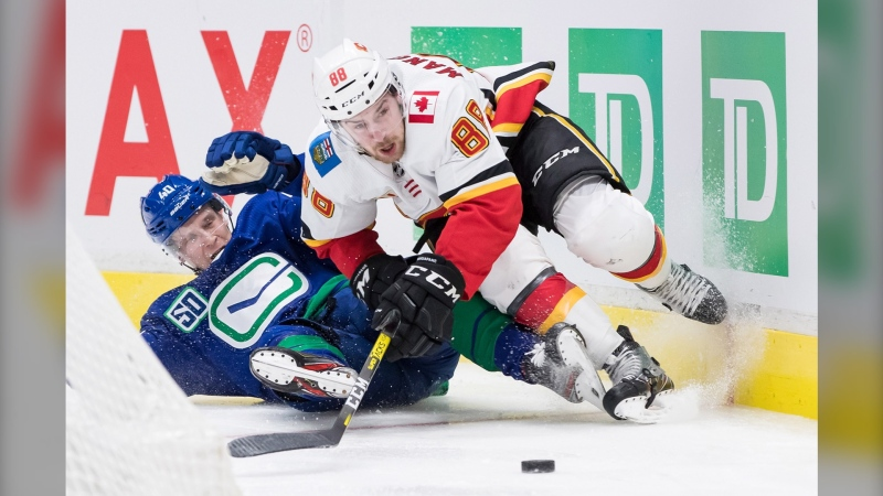 Vancouver Canucks' Elias Pettersson, left, of Sweden, hauls down Calgary Flames' Andrew Mangiapane and receives a penalty during the third period Saturday's game in Vancouver. (Darryl Dyck/The Canadian Press)