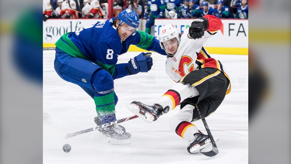 Vancouver Canucks' Chris Tanev, left, checks Calgary Flames' Johnny Gaudreau during the third period of Satruday's game in Vancouver. (Darryl Dyck/The Canadian Press)