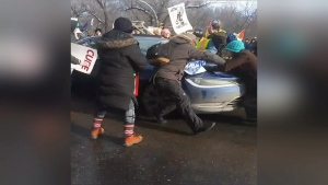 Tensions flared as a car pushed through a line of protesters blocking Albert St. on Saturday. (Courtesy: Brandyy-Lee Maxie)
