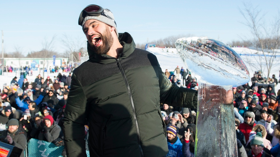 Super Bowl champion and Kansas City Chiefs player Laurent Duvernay-Tardif reacts next to an ice sculpture of the Vince Lombardi trophy during an event to celebrate his win in Montreal, Sunday, February 9, 2020. THE CANADIAN PRESS/Graham Hughes