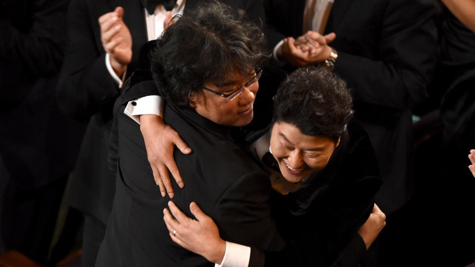 Bong Joon Ho, left, and Kang-Ho Song celebrate before going on stage to accept the award for best picture for
