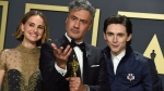 """Natalie Portman, from left, Taika Waititi, winner of the award for best adapted screenplay for """"Jojo Rabbit"""", and Timothee Chalamet pose in the press room at the Oscars on Sunday, Feb. 9, 2020, at the Dolby Theatre in Los Angeles. (Photo by Jordan Strauss/Invision/AP)"""