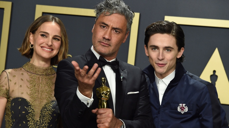 "Natalie Portman, from left, Taika Waititi, winner of the award for best adapted screenplay for ""Jojo Rabbit"", and Timothee Chalamet pose in the press room at the Oscars on Sunday, Feb. 9, 2020, at the Dolby Theatre in Los Angeles. (Photo by Jordan Strauss/Invision/AP)"