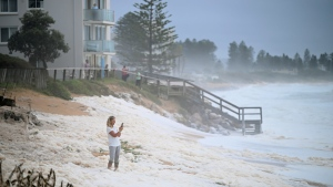 A resident inspects sea foam brought by waves approaching on beach front houses after heavy rain and storms at Collaroy in Sydney's Northern Beaches, Monday, February 10, 2020. (Joel Carrett, AAP Image via AP)