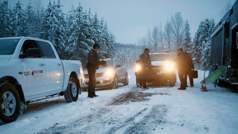 In this file photo, RCMP officers switch between shifts near their roadblock as supporters of the Unist'ot'en camp and Wet'suwet'en First Nation gather at a camp fire off a logging road near Houston, B.C., on Wednesday, January 9, 2019. THE CANADIAN PRESS/Chad Hipolito