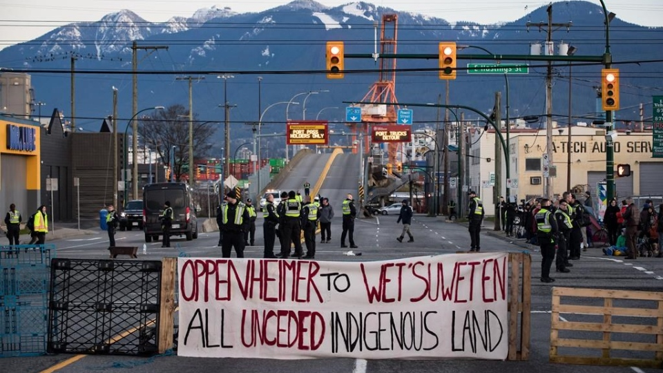 Police officers stand on the road after clearing the intersection of protesters that were blocking an entrance to the port during a demonstration in solidarity with Wet'suwet'en hereditary chiefs opposed to construction of a natural gas pipeline across their traditional territories, in Vancouver, on Monday February 10, 2020. THE CANADIAN PRESS/Darryl Dyck