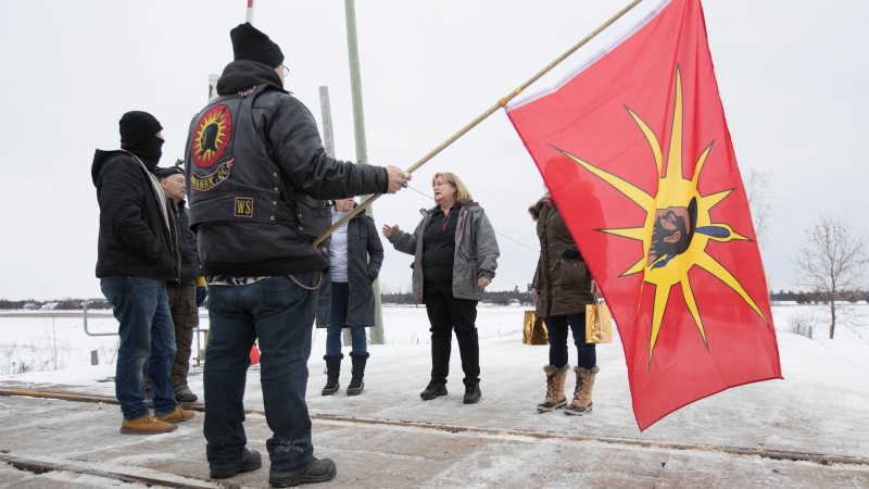 OPP Sgt. Diana Hampson, middle, speaks with members of the Mohawk Territory in Tyendinaga Mohawk Territory, near Belleville, Ont., on Tuesday, Feb. 11, 2020. THE CANADIAN PRESS/Lars Hagberg