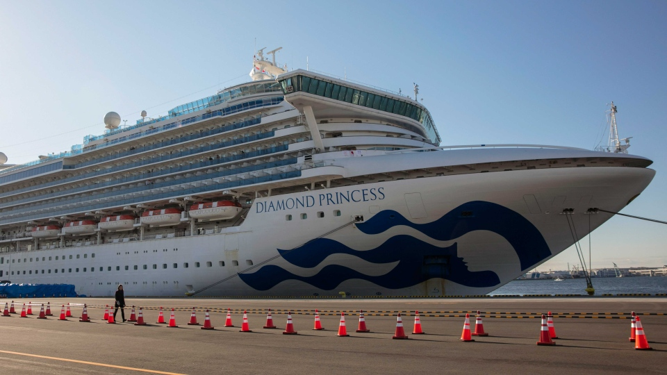A reporter walks near the quarantined Diamond Princess cruise ship in Yokohama, near Tokyo, Tuesday, Feb. 11, 2020. Japan's Health Minister Katsunobu Kato said the government was considering testing everyone remaining on board and crew on the Diamond Princess, which would require them to remain aboard until results were available. (AP Photo/Jae C. Hong)