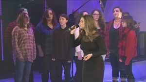 Angel Scott performs Hallelujah with a choir