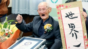 Chitetsu Watanabe, 112, poses next to the calligraphy he wrote after being awarded as the world's oldest living male by Guinness World Records, in Joetsu, Niigata prefecture, northern Japan Wednesday, Feb. 12, 2020. (Kyodo News via AP)