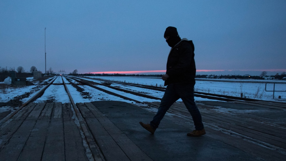 A First Nations protester walks over the train tracks in Tyendinaga Mohawk Territory near Belleville, Ontario, on Tuesday Feb. 11, 2020, in support of Wet'suwet'en's blockade of a natural gas pipeline in northern B.C. THE CANADIAN PRESS/Lars Hagberg
