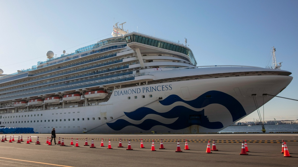 A reporter walks near the quarantined Diamond Princess cruise ship in Yokohama, near Tokyo, Tuesday, Feb. 11, 2020. (AP Photo/Jae C. Hong)