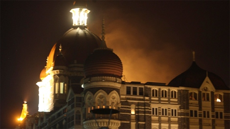 Smoke emerges from behind a dome on the Taj Hotel in Mumbai, India, after an attack on Wednesday, Nov. 26, 2008. (AP / Gautam Singh)