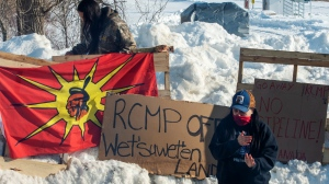 A member of the Mohawk community stands near the blockade of the commuter rail line Wednesday, February 12, 2020 in Kahnawake, Que.THE CANADIAN PRESS/Ryan Remiorz