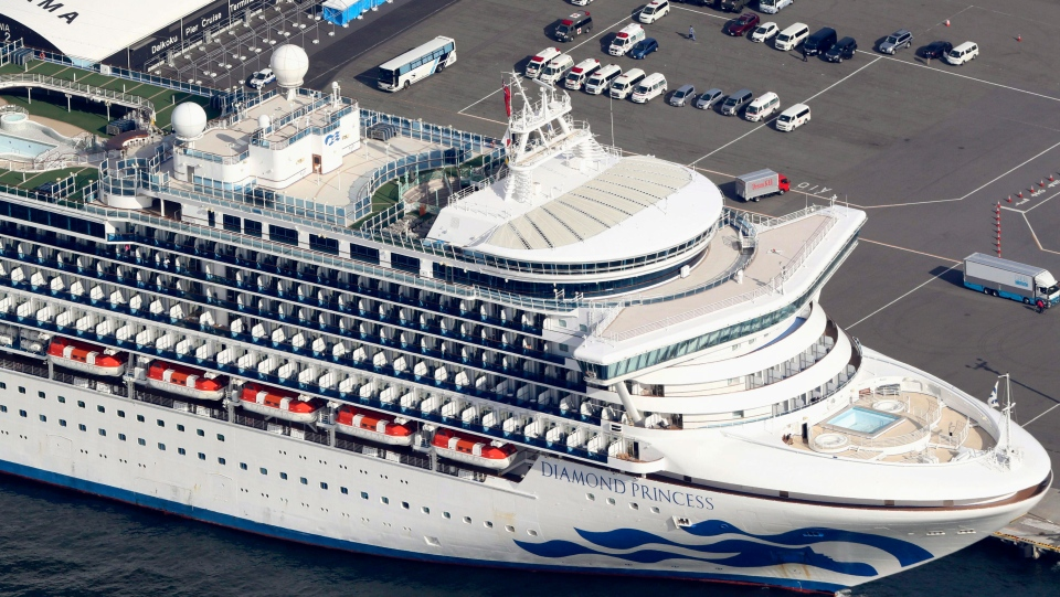 The U.S.-operated Diamond Princess is anchored as emergency vehicles stand by at Yokohama Port, near Tokyo, Wednesday, Feb. 12, 2020. Japan's Health Ministry said Wednesday that 39 new cases of a virus have been confirmed on the cruise ship quarantined at the Japanese port. (Kyodo News via AP)