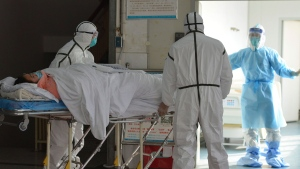 Medical workers in protective suits move a coronavirus patient into an isolation ward at the Second People's Hospital in Fuyang in central China's Anhui Province, Saturday, Feb. 1, 2020. Beijing criticized Washington's tightening of travel controls to bar most foreign nationals who visited the country within the past two weeks. (Chinatopix via AP)