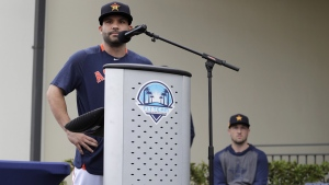 Houston Astros' Jose Altuve speaks at a podium as teammate Alex Bregman, seated right, looks on during a news conference in West Palm Beach, Fla., on  Feb. 13, 2020. (Jeff Roberson / AP)