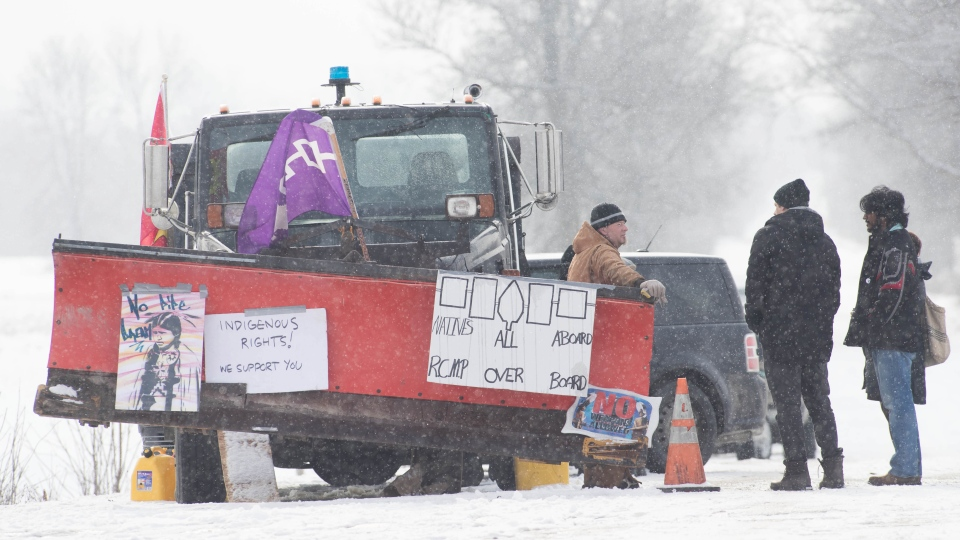 People stand near the train train tracks on day 8 of the train blockade in Tyendinaga, near Belleville, Ont., on Thursday Feb. 13, 2020, in support of Wet'suwet'en's blockade of a natural gas pipeline in northern B.C. THE CANADIAN PRESS/Lars Hagberg