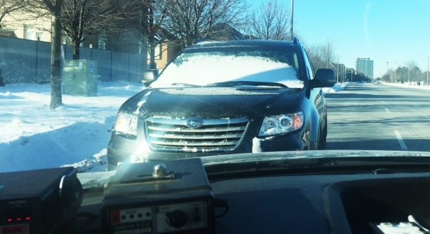 Motorist driving with snow-covered windshield pulled over by cops