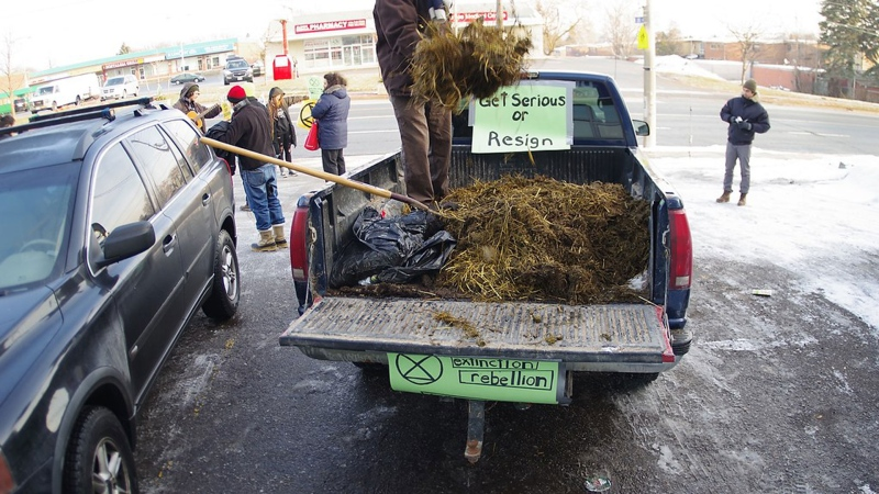 Members of Extinction Rebellion dump manure in front of premier Doug Ford's office in Etobicoke. (Extinction Rebellion)