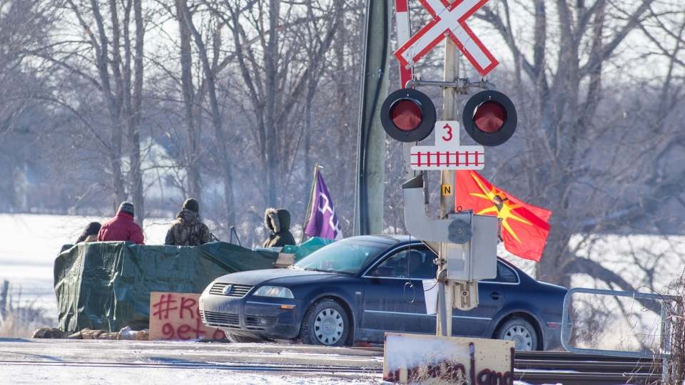Protesters stand on the closed train tracks on the ninth day of the blockade in Tyendinaga Mohawk Territory, near Belleville, Ont., Friday, Feb. 14, 2020. THE CANADIAN PRESS/Lars Hagberg