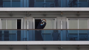 A quarantined passenger on the Diamond Princess cruise ship stretches on the balcony of his cabin Saturday, Feb. 15, 2020, in Yokohama, near Tokyo. (AP Photo/Jae C. Hong)