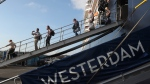 Passengers of the MS Westerdam, owned by Holland America Line disembark from the MS Westerdam, at the port of Sihanoukville, Cambodia, Saturday, Feb. 15, 2020. After being stranded at sea for two weeks because five ports refused to allow their cruise ship to dock, the passengers of the MS Westerdam were anything but sure their ordeal was finally over. (AP Photo/Heng Sinith)