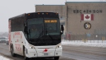 A bus drives on Old Highway 2 after leaving the Yukon Lodge, which will temporarily house passengers from a charter flight from the centre of the global novel coronavirus outbreak in Wuhan, China, at CFB Trenton, in Trenton, Ont., on Feb. 7, 2020. THE CANADIAN PRESS/Justin Tang