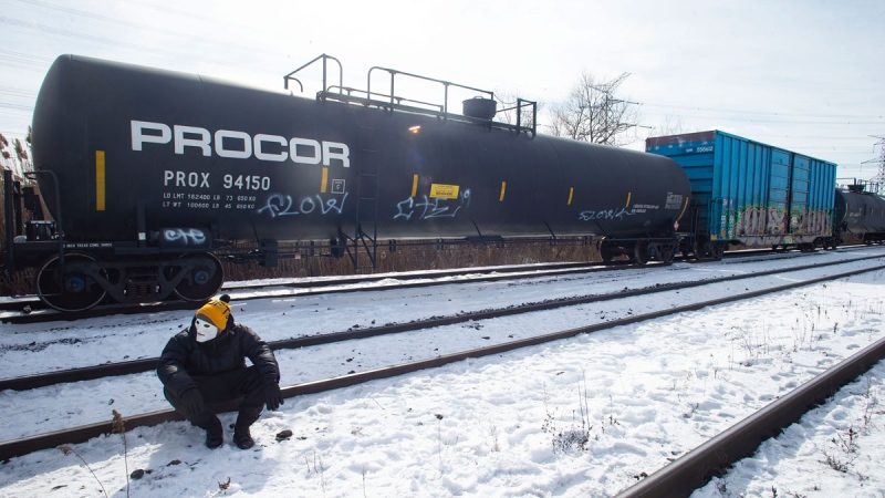 A protestor sits on train tracks during a blockade of the rail line at Macmillan Yard in Toronto, Saturday, Feb. 15, 2020. The protest is in solidarity with the Wet'suwet'en hereditary chiefs opposed to the LNG pipeline in northern British Columbia. THE CANADIAN PRESS/Chris Young