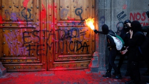"""A masked, female protester sprays fire at the entrance to the National Palace, the presidential office and residence, after demonstrators covered it in fake blood and the Spanish message: """"Femicide State,"""" in Mexico City, Friday, Feb. 14, 2020. (AP Photo/Ginnette Riquelme)"""