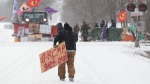 A protester carries a sign at a rail blockade on the tenth day of demonstration in Tyendinaga, near Belleville, Ont., Saturday, Feb. 15, 2020. THE CANADIAN PRESS/Lars Hagberg