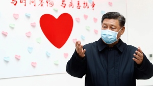 In this Feb. 10, 2020, photo released by Xinhua News Agency, Chinese President Xi Jinping gestures near a heart shape sign and the slogan 'Race against time, Fight the Virus' during an inspection of the centre for disease control and prevention of Chaoyang District in Beijing. Xi said on Wednesday, Feb. 12, 2020, that he is promising tax cuts and other aid to industries hurt by a virus outbreak in a renewed effort to rein in the rising damage to the economy. (Liu Bin/Xinhua via AP, File)