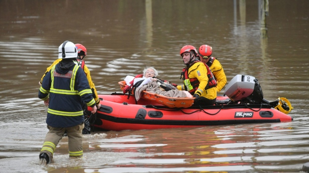 """A member of the public is rescued after flooding in Nantgarw, Wales, Sunday, Feb. 16, 2020. Storm Dennis roared across Britain on Sunday, lashing towns and cities with high winds and dumping so much rain that authorities urged residents to protect themselves from """"life-threatening floods"""" in Wales and Scotland. (Ben Birchall/PA via AP)"""