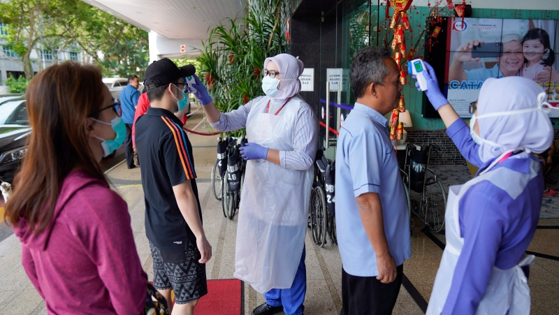 In this Feb. 5, 2020, file photo, nurses check the temperatures of visitors as part of the coronavirus screening procedure at a hospital in Kuala Lumpur, Malaysia. (AP Photo/Vincent Thian, File)