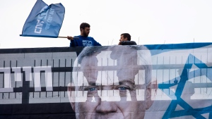 Blue and White party activists stands behind an election campaign billboard that shows the party's leader Benny Gantz, in Tel Aviv, Israel, Sunday, Feb. 16, 2020. (AP Photo/Oded Balilty)