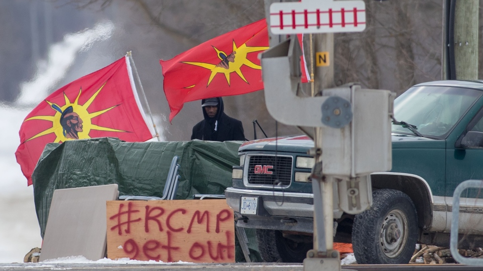 A protester stands between Mohawk Warrior Society flags at a rail blockade on the tenth day of demonstration in Tyendinaga, near Belleville, Ont., Sunday, Feb. 16, 2020. (THE CANADIAN PRESS / Lars Hagberg)