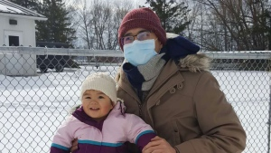 Richard Fabic and his 15-month-old daughter Chloe play in the snow outside a Canadian Forces Base in Trenton where they remain in isolation following Chloe's return from Wuhan. (Provided by Richard Fabic)